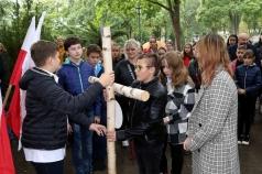 Na zdjęciu uczniowie przekazujący sobie drewniany krzyż