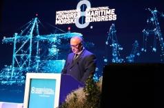 Mężczyzna przy mównicy przemawiający do mikrofonu. W tle grafika 8. Międzynarodowego Kongresu Morskiego