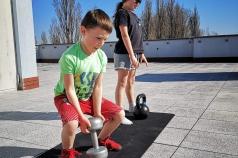 Na zdjęciu znajduje się chłopiec ćwiczący z hantlą oraz dziewczynka ćwicząca z kulą  kettlebell
