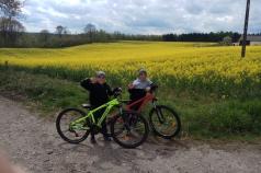 Na zdjęciu jest 2 chłopców z rowerami. W tle pole rzepaku