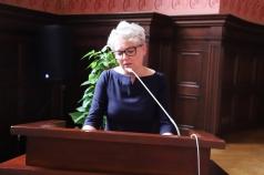 Kobieta stoi przy mównicy i przemawia do mikrofonu