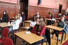 Grupa uczniów siedząca w ławkach w auli szkolnej