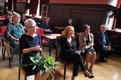 Grupa osób siedzących na krzesłach w auli szkolnej. Kobieta po lewej stronie ma na kolanach bukiet kwiatów