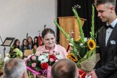 Uczeń wręcza starszej kobiecie bukiet kwiatów