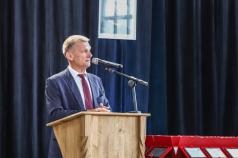 Mężczyzna stoi przy mównicy i przemawia do mikrofonu