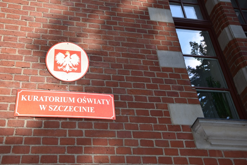 Na zdjęciu znajduje się tablica z Godłem Polski oraz tablica z napisem Kuratorium Oświaty w Szczecinie