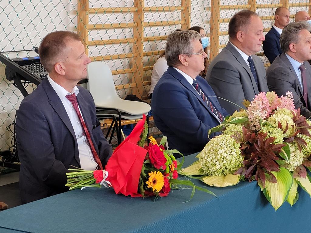 Na zdjęciu 4 mężczyzn siedzących za stołem. Na stole wiązanki kwiatów.