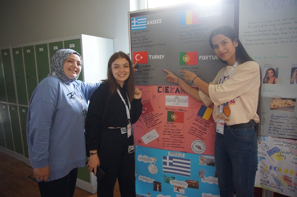 Na zdjęciu 3 dziewczyny na tle tablicy, wskazują palce na flagę Turcji