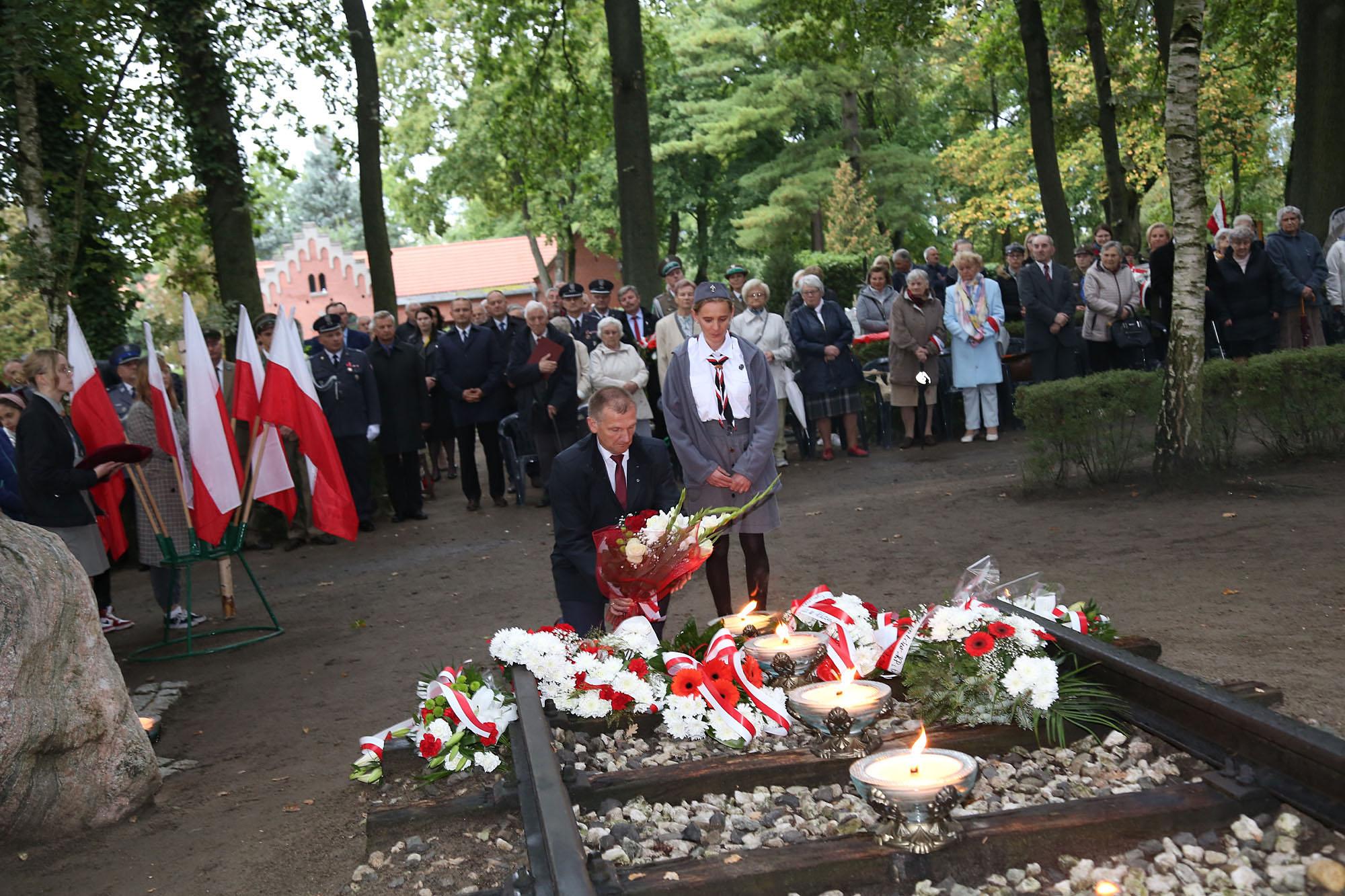 Na zdjęciu klęczący mężczyzna składający kwiaty pod pomnikiem. Obok niego stoi harcerka