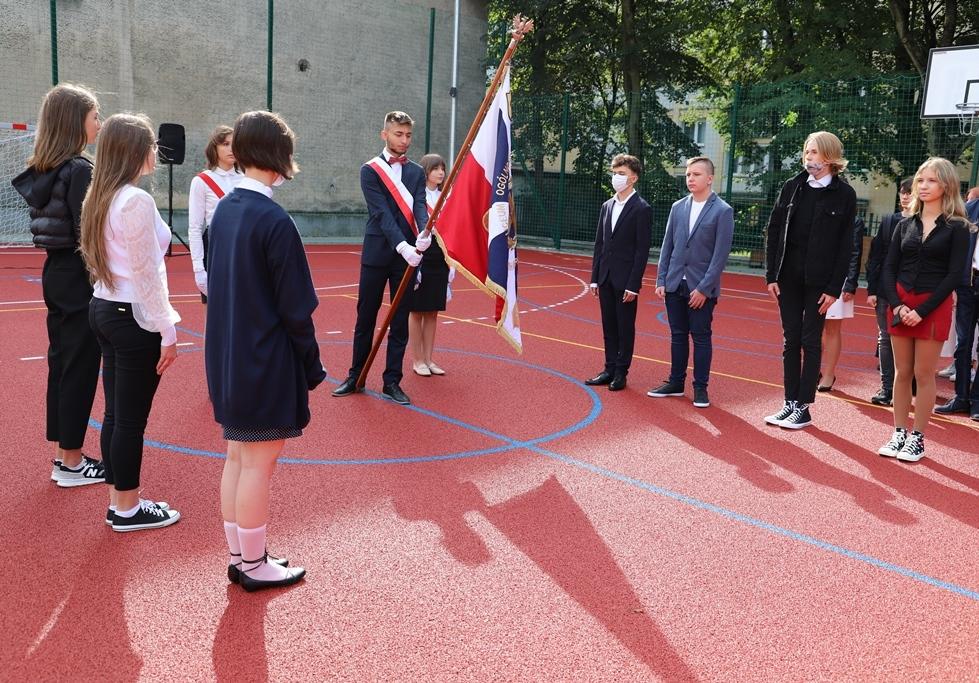 Na zdjęciu grupa uczniów oraz chłopak trzymający sztandar szkoły
