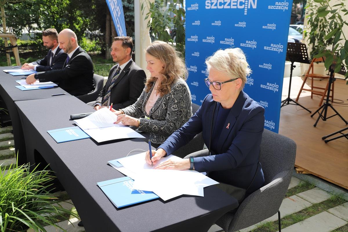 Grupa osób siedzi przy stole i podpisuje dokumenty