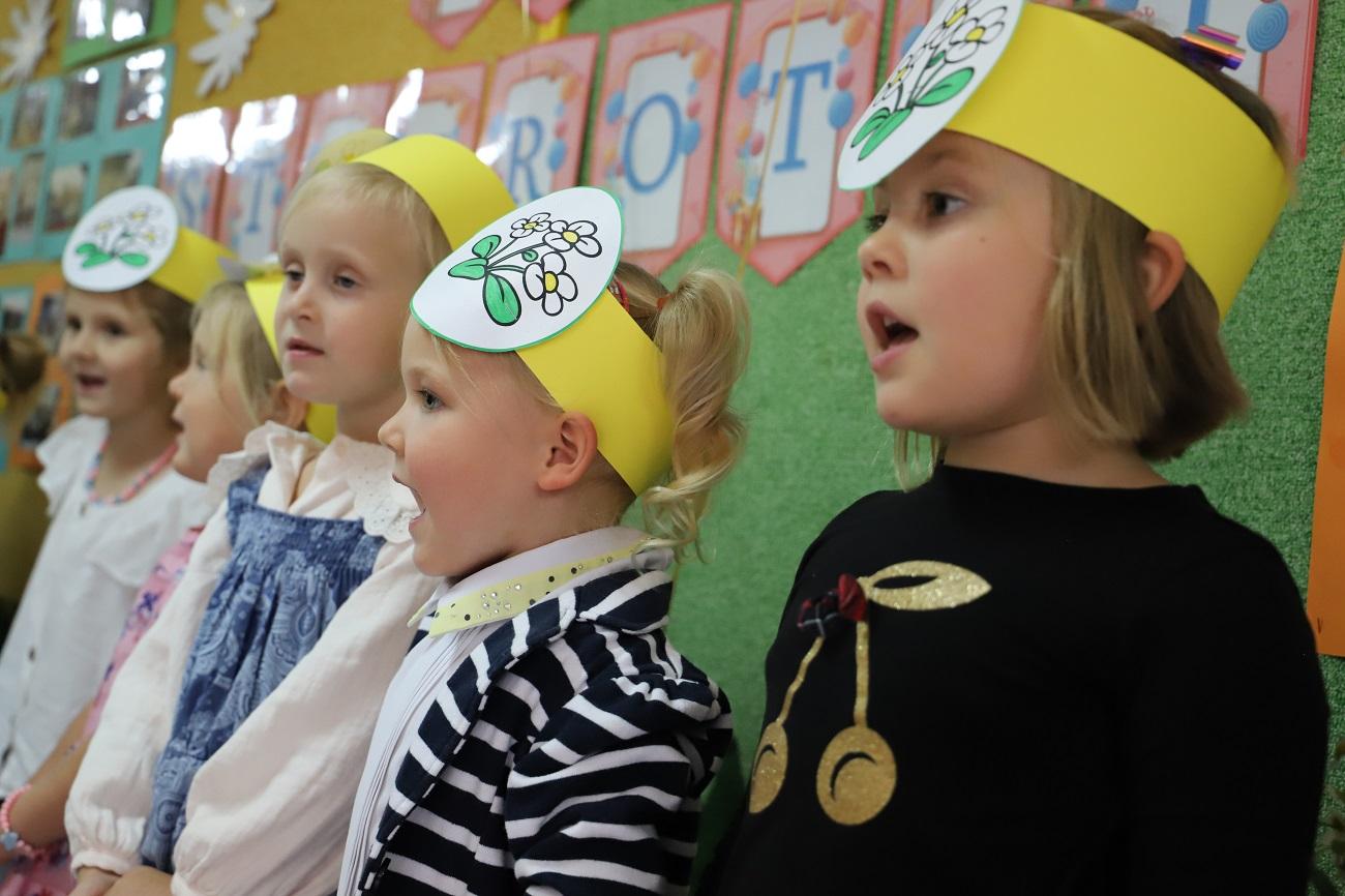 Na zdjęciu pięć śpiewających dziewczynek. Dziewczynki mają na głowie żółtą opaskę a na niej doczepiony rysunek stokrotki